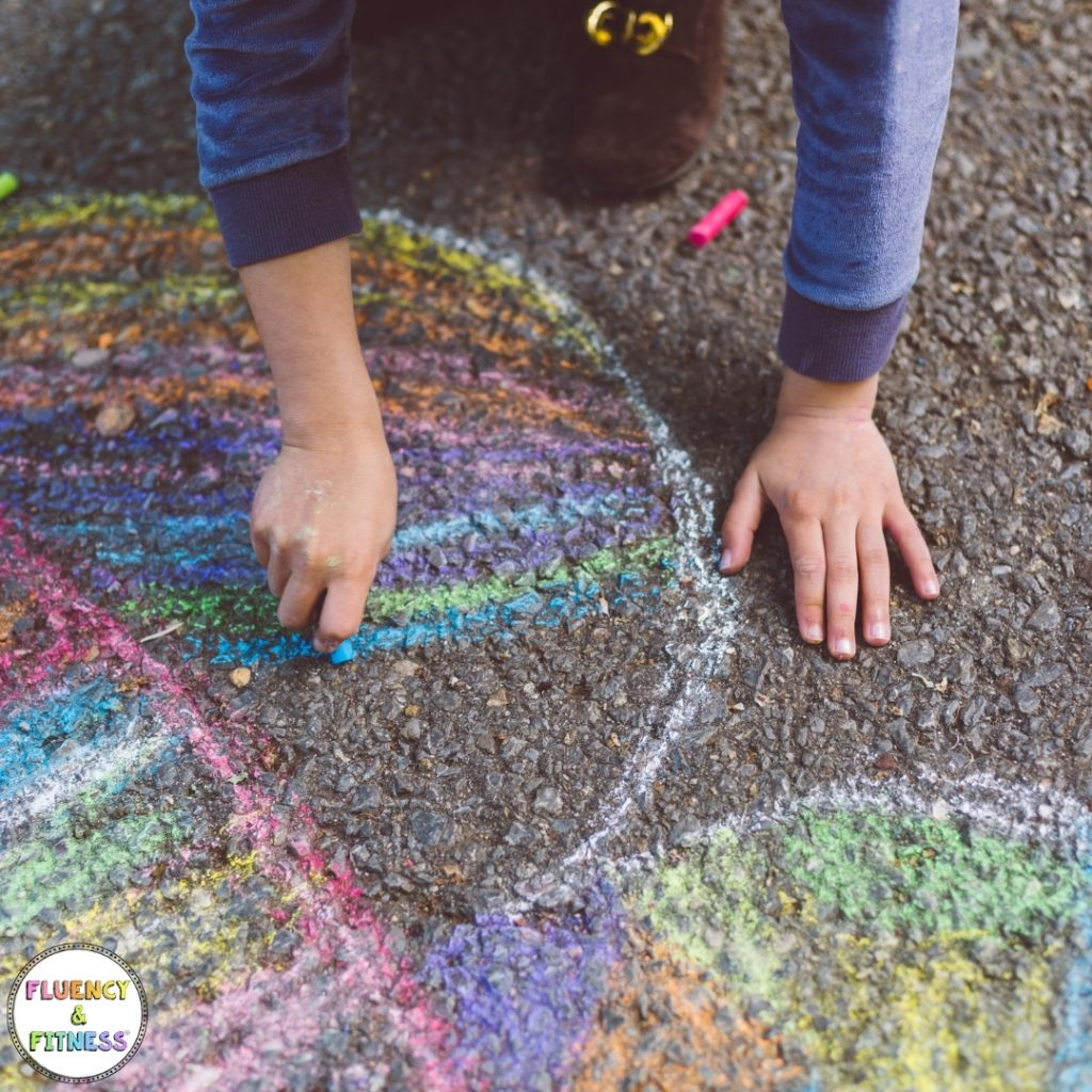 Child drawing outside with chalk